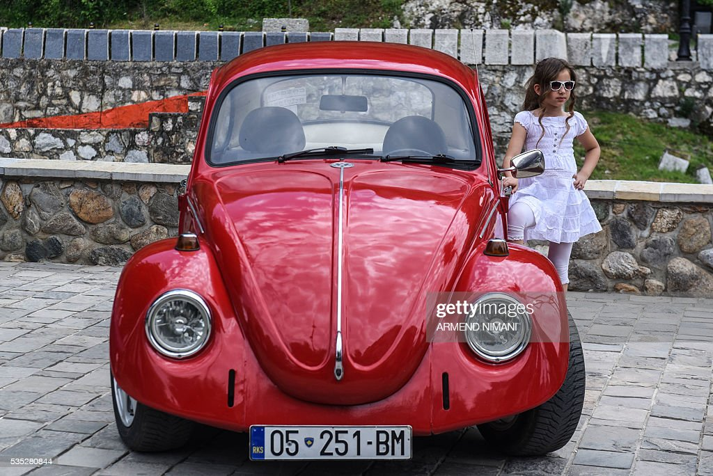A young girl poses in front of a vintage car displayed during the 11th Old Timers Fest on May 29, 2016 in Prizren. / AFP / ARMEND