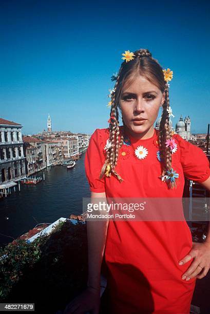 A young girl posing showing off a bizarre hairstyle with braids decorated by coloured daisies Venice 1960s
