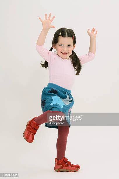 A young girl posing with her arms raised and one foot raised