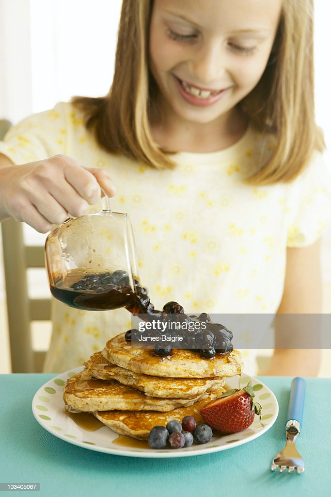 Young girl pouring blueberry syrup over pancakes : Stock Photo