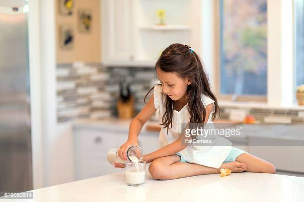 Young girl pours a glass of milk on the counter