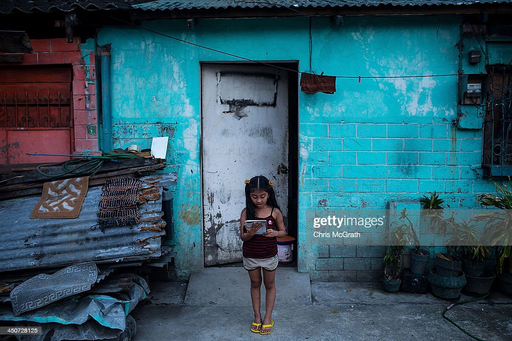 A young girl practices her singing on the roadside in front of her house following the recent super typhoon on November 20 2013 in Leyte Philippines...