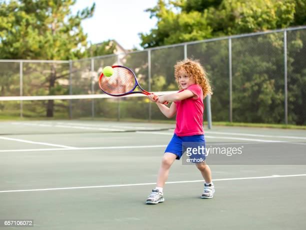 Young Girl Practicing Playing Tennis