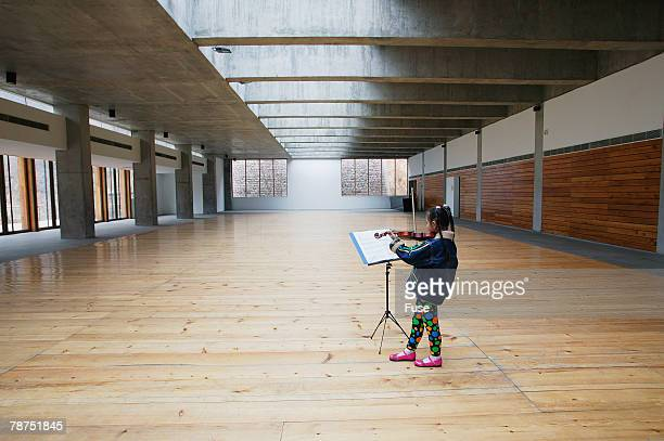 Young Girl Practicing Violin in Empty Hall