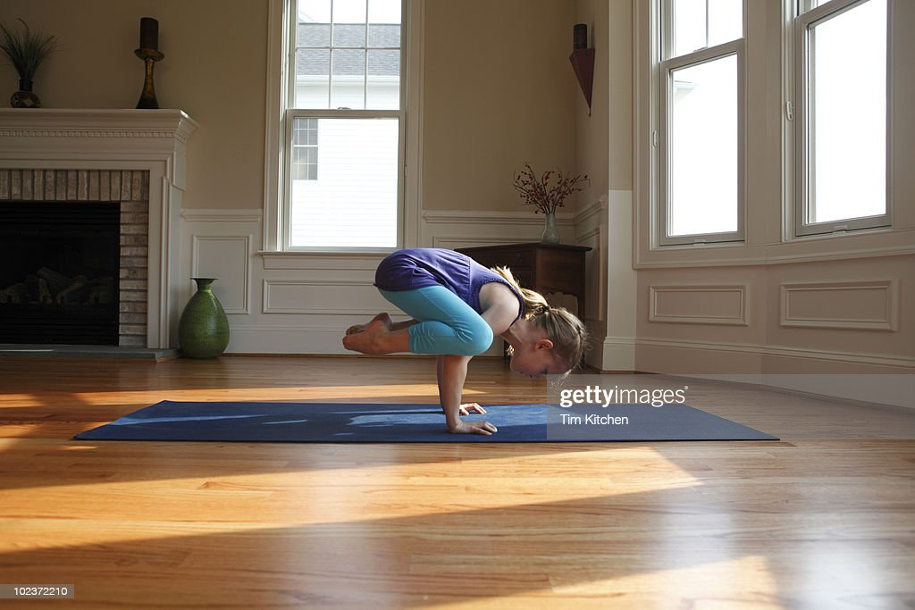 Young girl practicing yoga in home, crow pose : Stock Photo