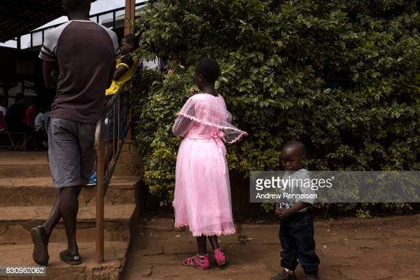 A young girl prays during Sunday service at Our Lady of Guadalupe Parish in the Kibera slum on August 13 2017 in Nairobi Kenya A day prior...