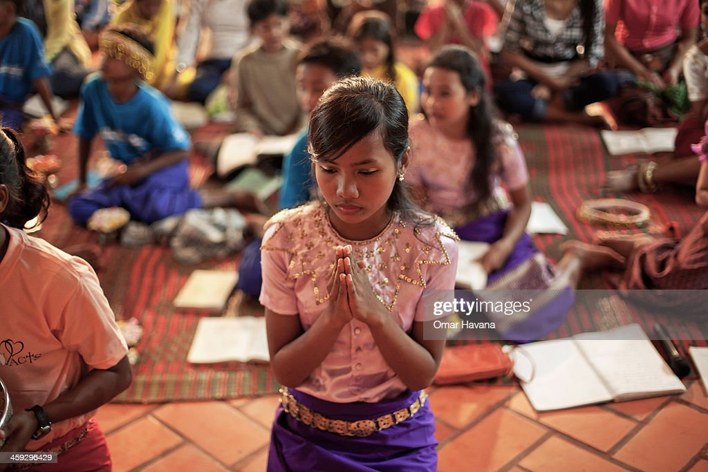 A young girl prays during the Christmas Eve mass at the church of Tahen Village on December 24, 2013 in Battambang, Cambodia. The parish at Battambang dates back to 1790 when the Catholic community first arrived. Now they serve around 1000 Catholics and 600 families.