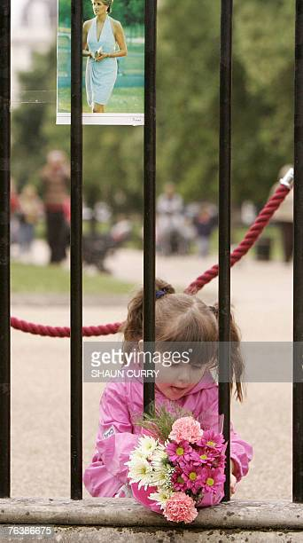 A young girl prepares to place flowers at the gates to Kensington Palace in central London 30 August 2007 on the eve of the tenth anniversary of the...