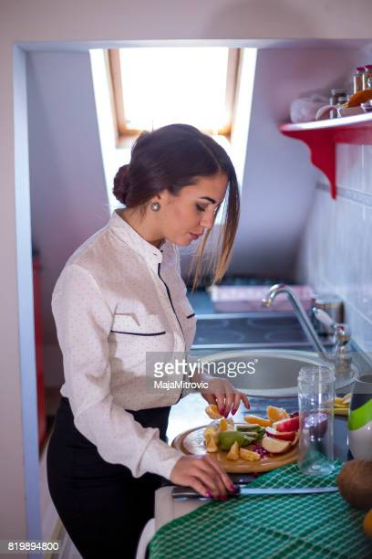 Young girl preparing fruit salad. Fresh fruits on the wooden table, closeup.