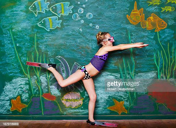 A young girl pretending to snorkel.