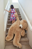 Young girl pulling a large teddy bear up stairs
