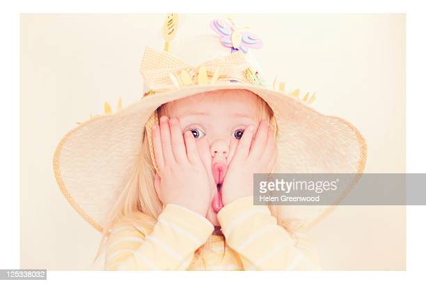 Young girl pulling faces in Easter bonnet
