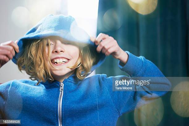 young girl pulling hood over head