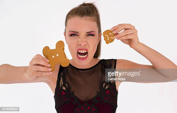 Young girl pulling the head off a gingerbread man