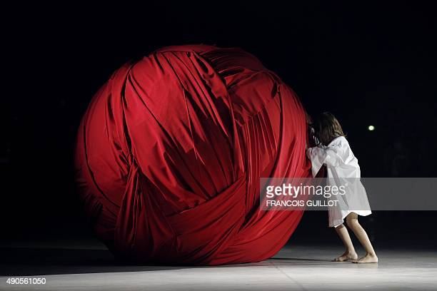 A young girl pushes a giant ball made of fabric during Jacquemus' fashion show during the 2016 Spring/Summer readytowear collection on September 29...