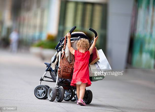 Young girl pushing a baby carriage with shopping bags
