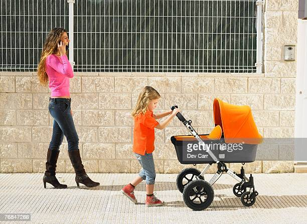 Young girl (5-7) pushing buggy on pavement while mother talks on mobile phone, Alicante, Spain,