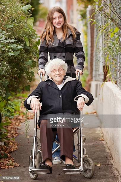 Junges Mädchen im Rollstuhl Schieben Großmutter