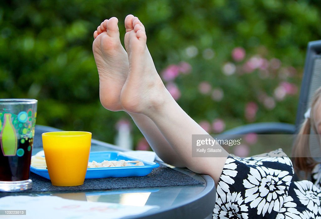 Young girl puts bare feet on table : Stock Photo