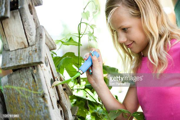 Young girl putting bird seed in birdhouse