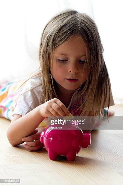 Young girl putting coin in piggy bank