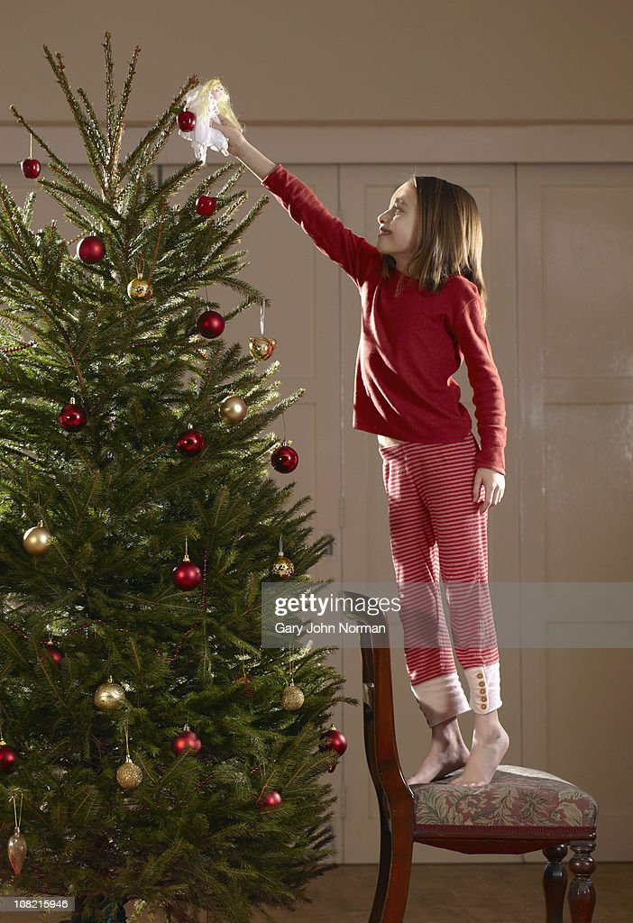 Young girl putting fairy on tree : Stock Photo