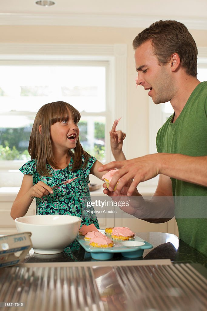 Young girl putting icing on older brother's nose : Stock Photo