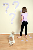 Young girl putting sticky notes on a wall