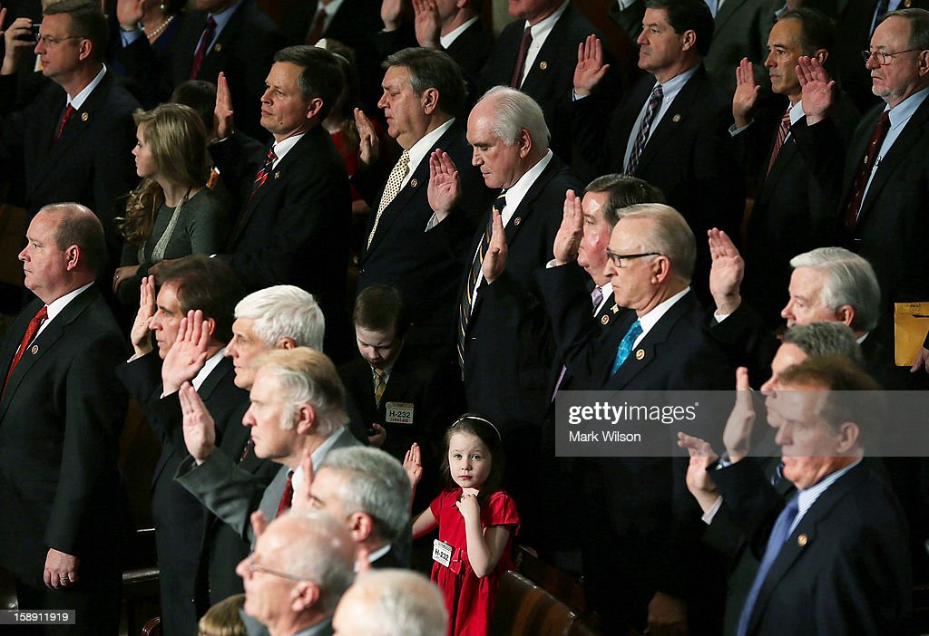 A young girl raises her right hand as newly elected members are sworn in during the first session of the 113th Congress in the House Chambers January 3, 2013 in Washington, DC. House Speaker Boehner was re-elected as Speaker and presided over the swearing in of the newly elected members of the 113th Congress.