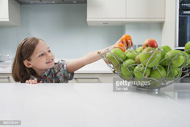 Young girl reaching for a tangerine from the fruit bowl