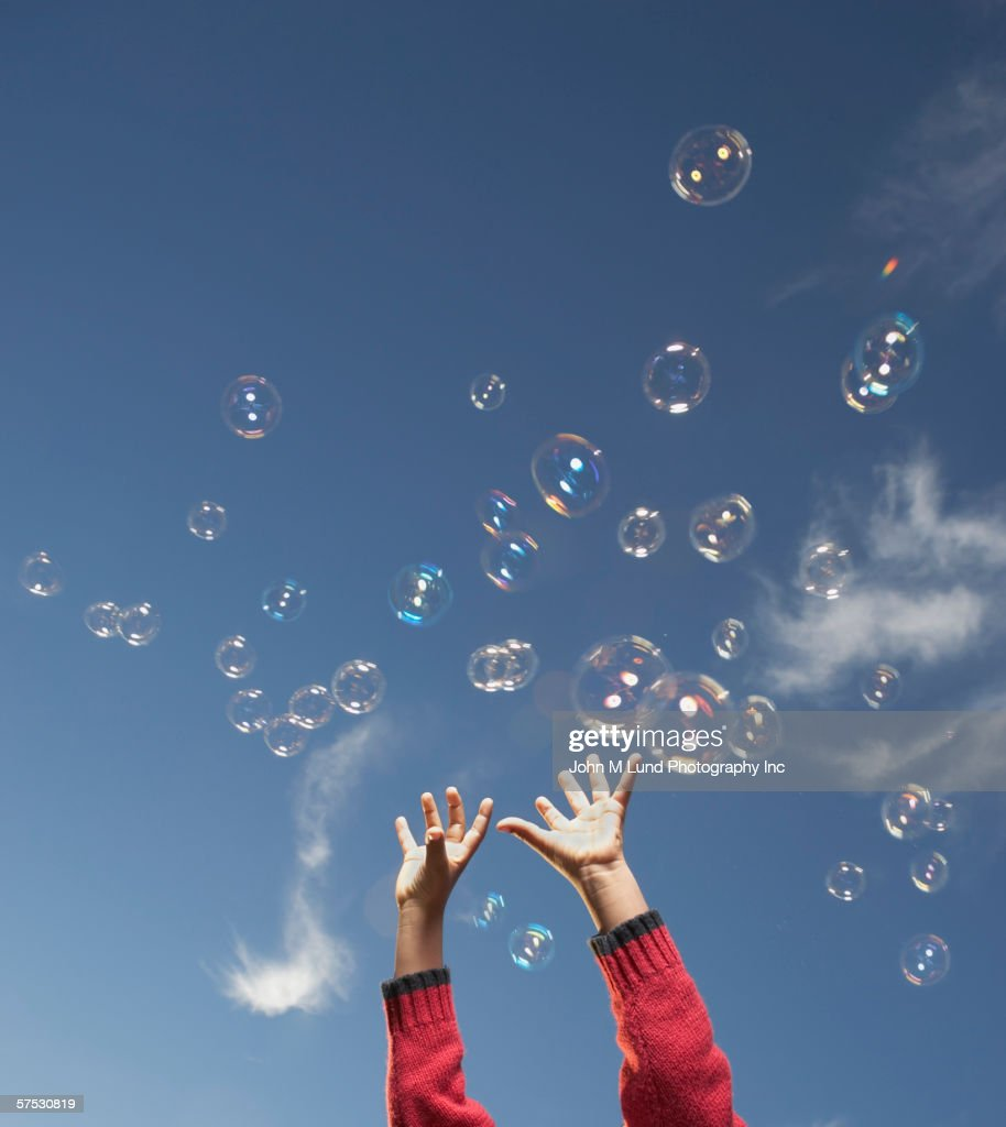 Young girl reaching for airborne bubbles : Stock Photo