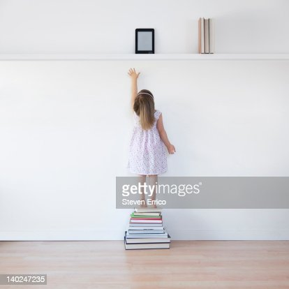 Young girl reaching for electronic book reader : Stock Photo