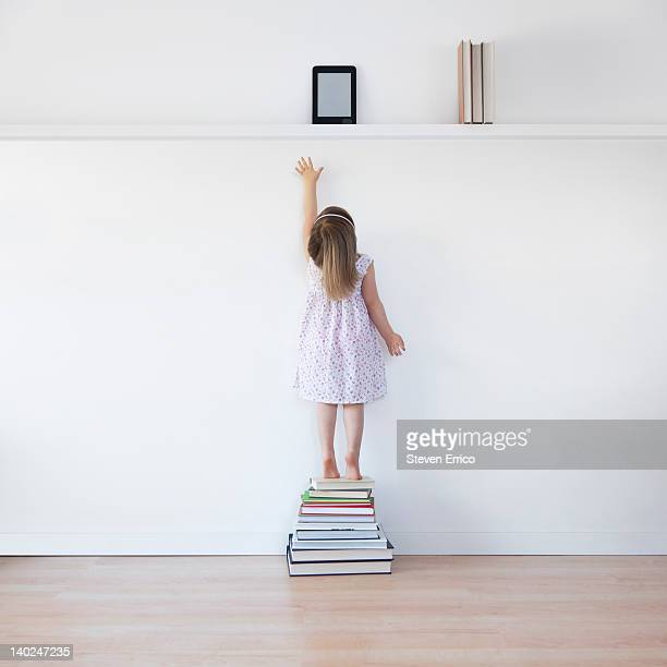 Young girl reaching for electronic book reader