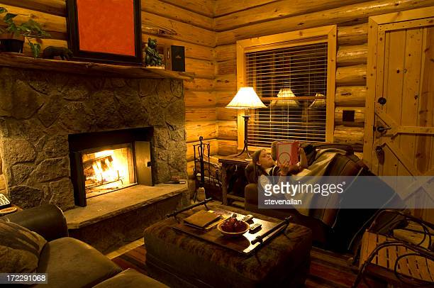 Young girl reading a book next to a fireplace