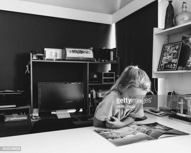 Young girl reading a book on the kitchen benchtop