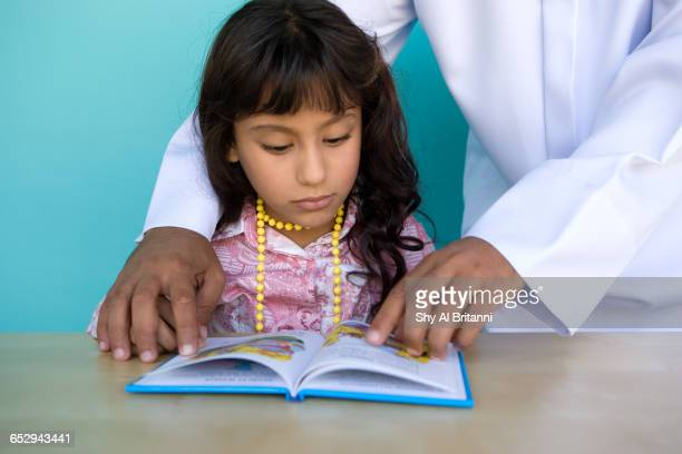 A young girl reading a book.