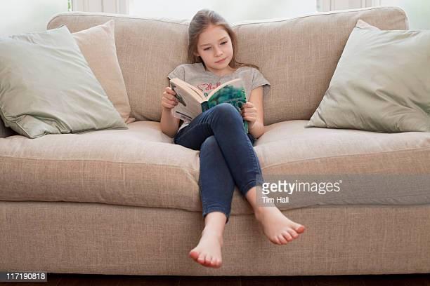 Giovane ragazza lettura libro sul divano