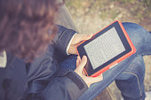 young girl sitting on a bench at park and reading E-book