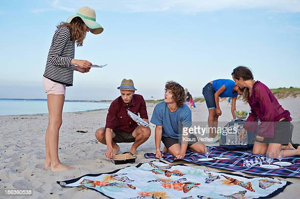 Young girl reading instructions for grill at beach