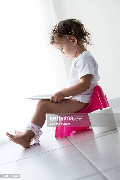 Young girl reading on potty