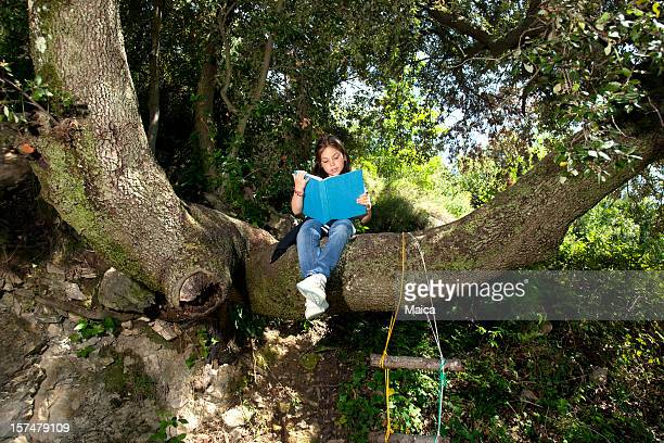 Young girl reading sitting on a tree branch