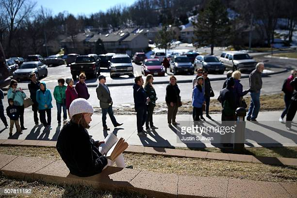 A young girl reads a book as people wait in line to enter a 'get out to caucus' event for democratic presidential candidate former Secretary of State...