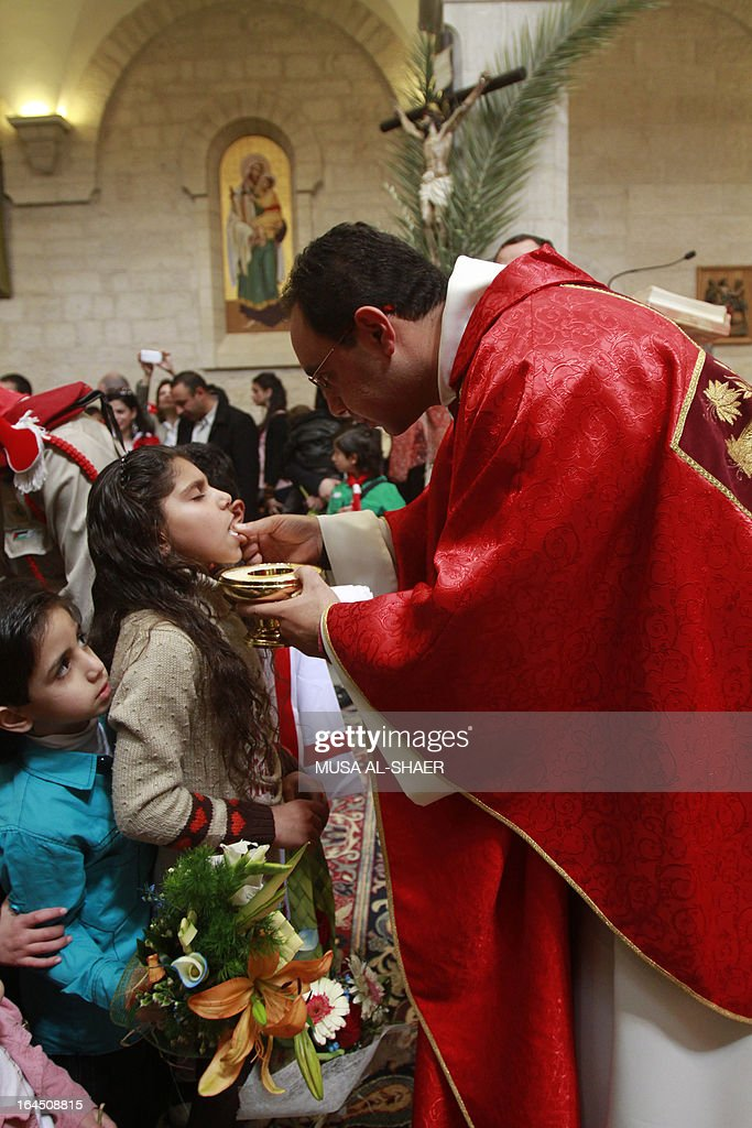 A young girl receives the Holy communion during a mass marking the Palm Sunday at the Church of Santa Cathrina in the Church of the Nativity Compound in the West Bank city of Bethlehem on March 24, 2013. Palm Sunday marks the triumphant return of Jesus Christ to Jerusalem when a cheering crowd greeted him waving palm leaves, a week before his crucifixion. AFP PHOTO/MUSA AL-SHAER