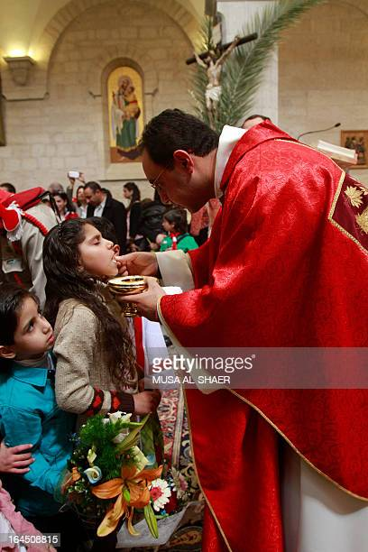 A young girl receives the Holy communion during a mass marking the Palm Sunday at the Church of Santa Cathrina in the Church of the Nativity Compound...