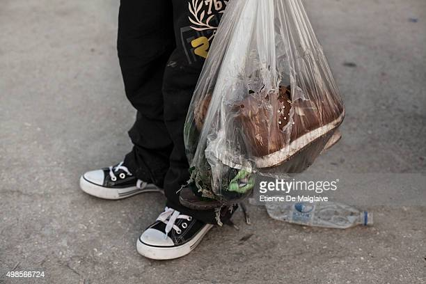 A young girl refugee carries a teared plastic bag containing shoes at the Moria transit camp where refugees stay for a lengthy registration process...