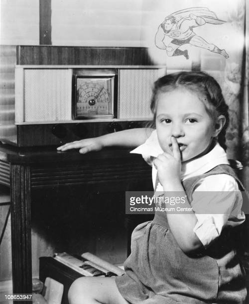 A young girl requests quiet by placing her index finger to her mouth as she sits next to a radio Cincinnati OH 1948 Above her is a drawing of the...
