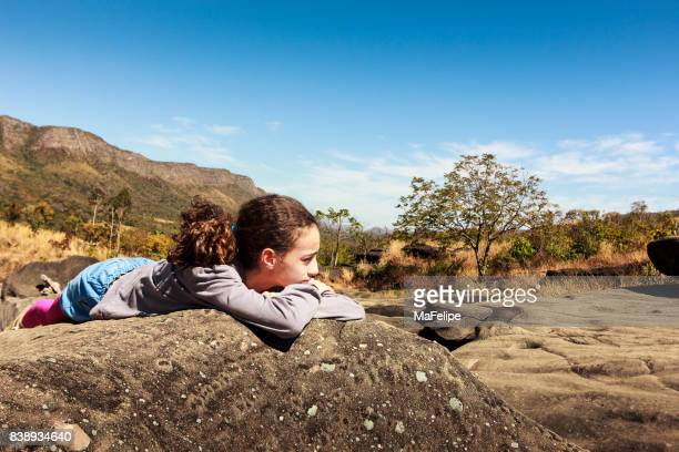 Young girl resting over a rock on Vale da Lua (Moon Valley)