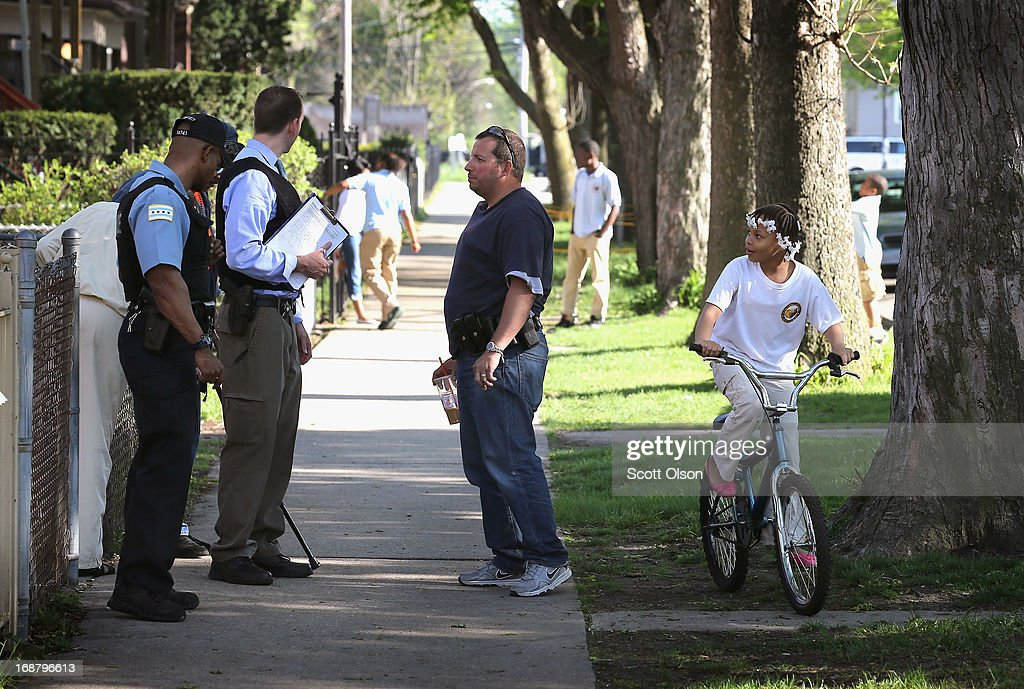 A young girl rides her bike by Chicago Police officers investigating the scene of a shooting in the South Shore neighborhood on May 14, 2013 in Chicago, Illinois. A trail of blood ran from where one of the victims was shot, down the sidewalk, past the point where the officers were standing. The shooting was the first of several that left two men dead and 11 others wounded in the city between Monday afternoon and the early hours of Tuesday morning.
