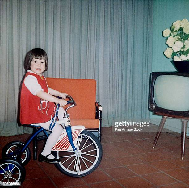 Young girl rides her new tricycle in the house ca 1967