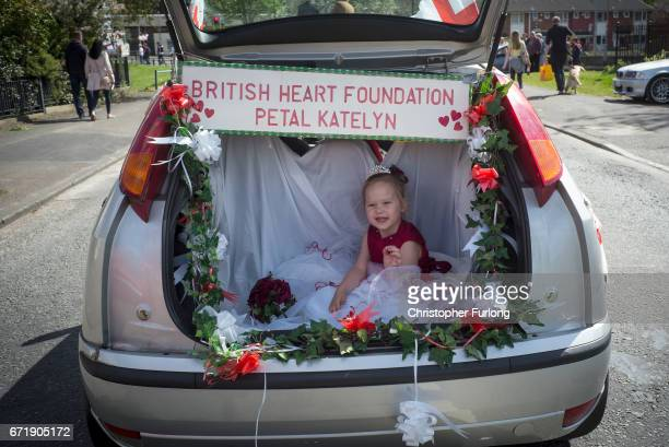 A young girl rides in the boot of a car during the Manchester St George's Day parade through the streets on April 23 2017 in Manchester England...
